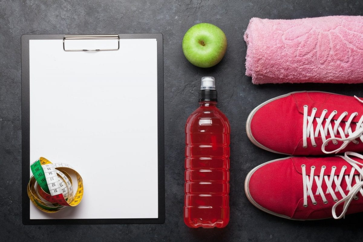 After-workout mistakes that trigger weight gain. Fitness equipment and blank sheet for workout