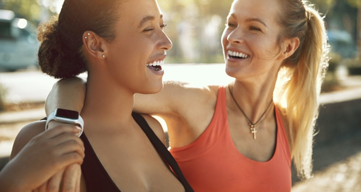 12 ways to get yourself to exercise every day.Laughing friends in sportswear standing outside on a sunny day
