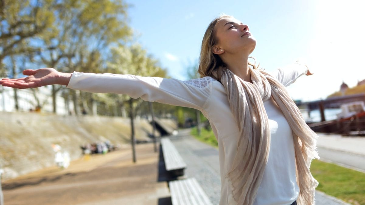 3 surprising benefits of weight-loss surgery. Pretty young woman enjoying the spring with arms raised to the s