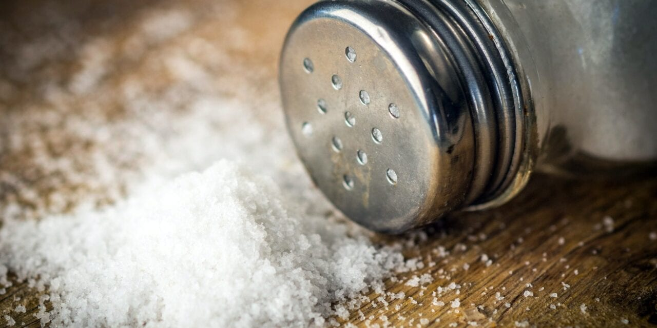 Reduced sodium intake leads to faster weight loss. Salt on wooden background