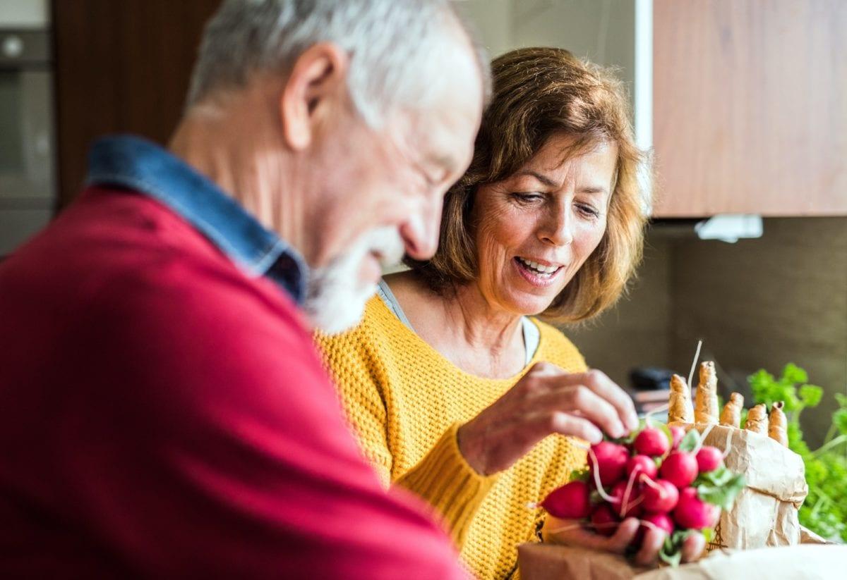 10 ways to make each day healthier. Senior couple preparing food in the kitchen.