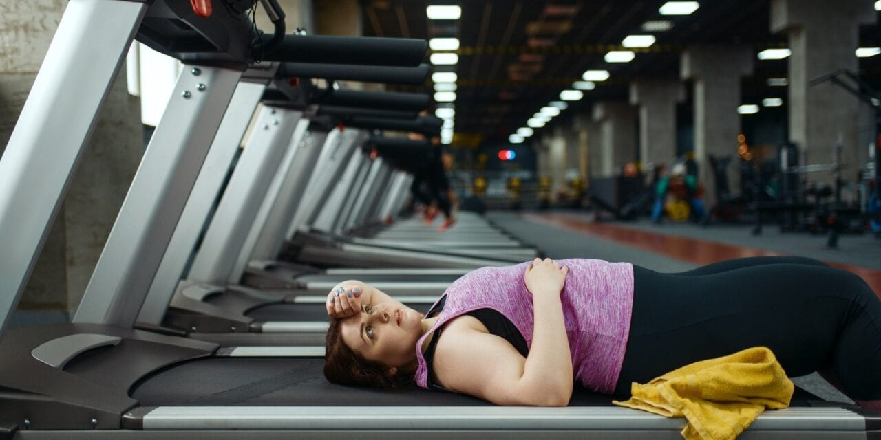 12 signs you might be exercising too much. Tired overweight woman lying on treadmill in gym