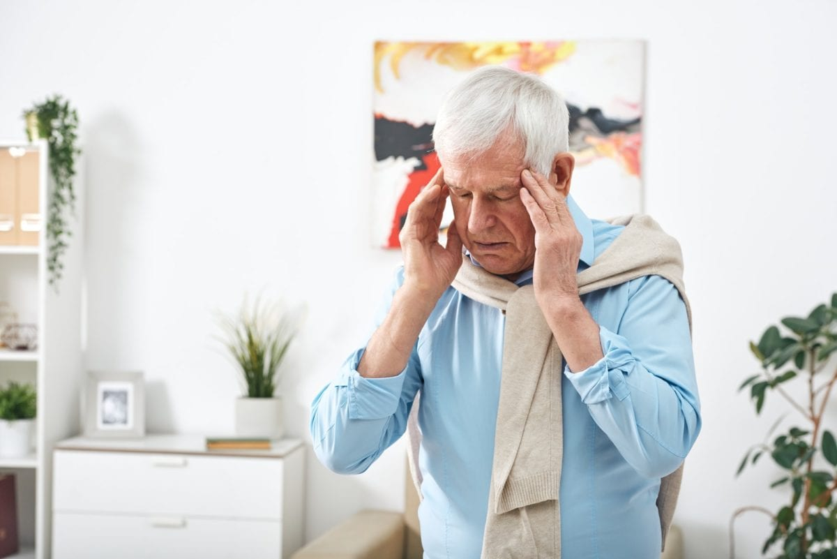 11 signs that indicate high blood sugar. Tired senior man in blue shirt touching his temples while feeling headache