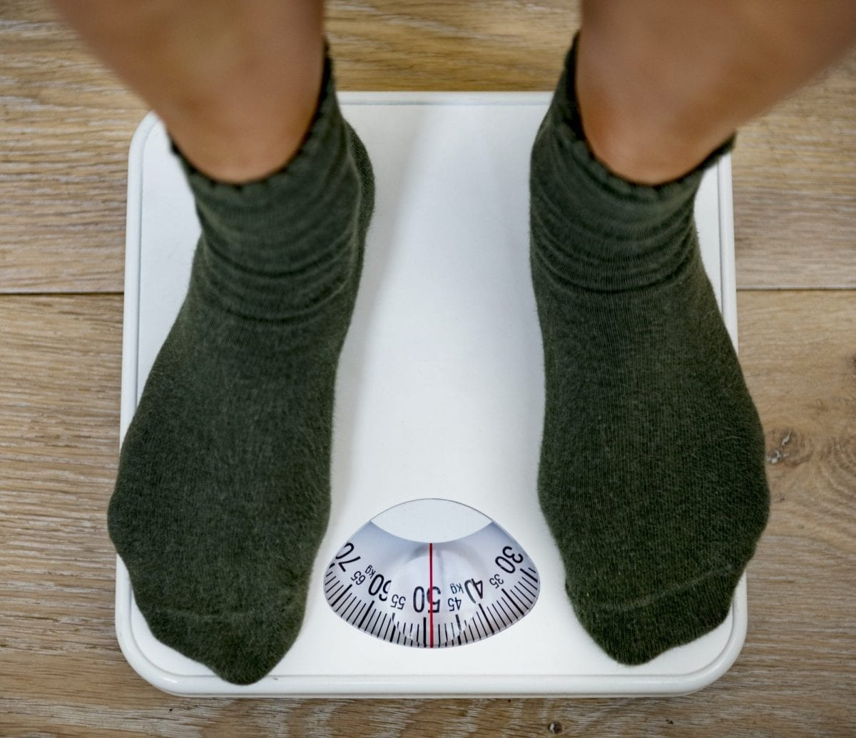 5 reasons you might be failing at weight loss. Woman on a weight scale