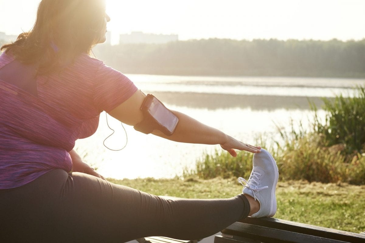 4 ways to care for sore muscles. Woman warming up before running