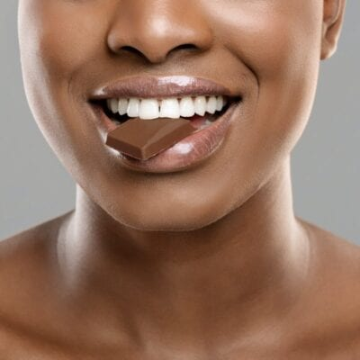 Healthy candy swaps that satisfy your sweet tooth. Afro Woman Biting Milk Chocolate Slice With Her White Healthy Teeth