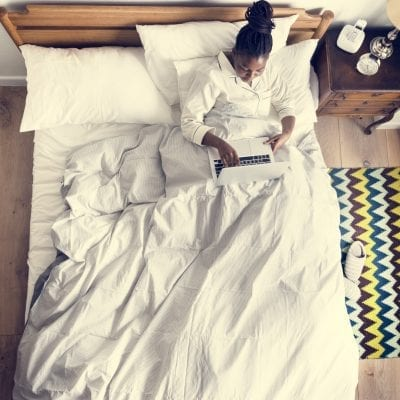 African American woman on bed using a laptop