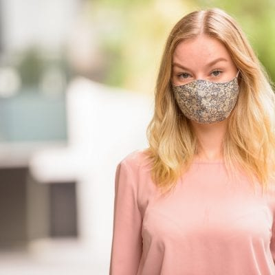 Face of young blonde woman wearing mask in the city with nature outdoors