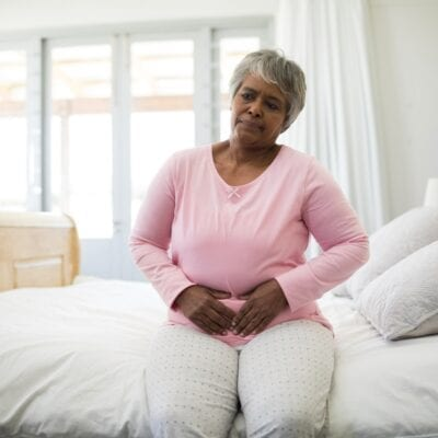 Senior woman having a huge stomach pain in bedroom
