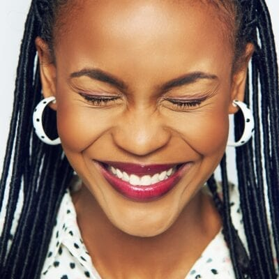 Smiling pretty black woman holding eyes closed