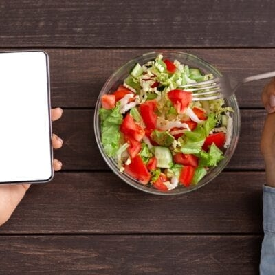Woman using smartphone with blank screen and eating fresh salad