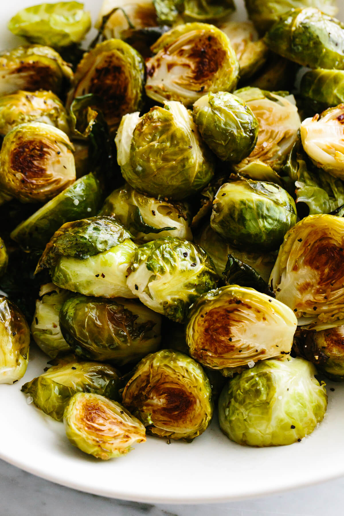Roasted brussels sprouts in a large white bowl.