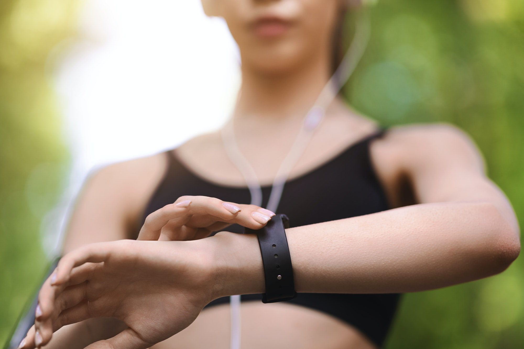 Gadgets For Sport. Female athlete using smartwatch outdoors to track training progress