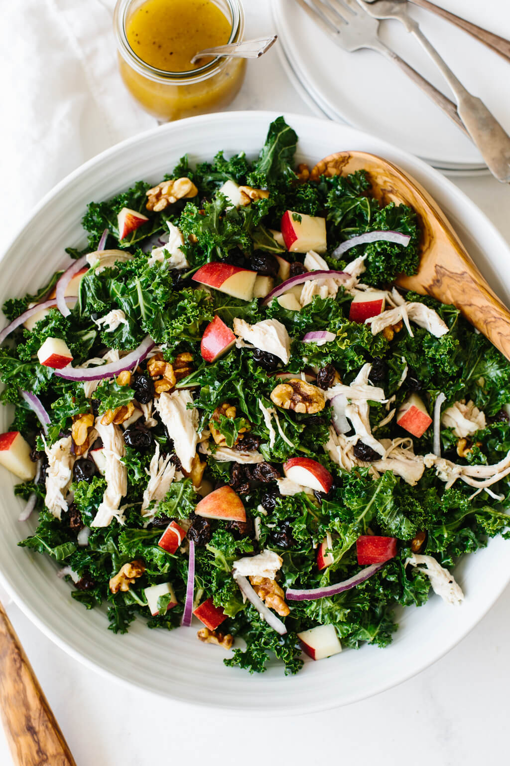 Kale salad with chicken and apples on a white table
