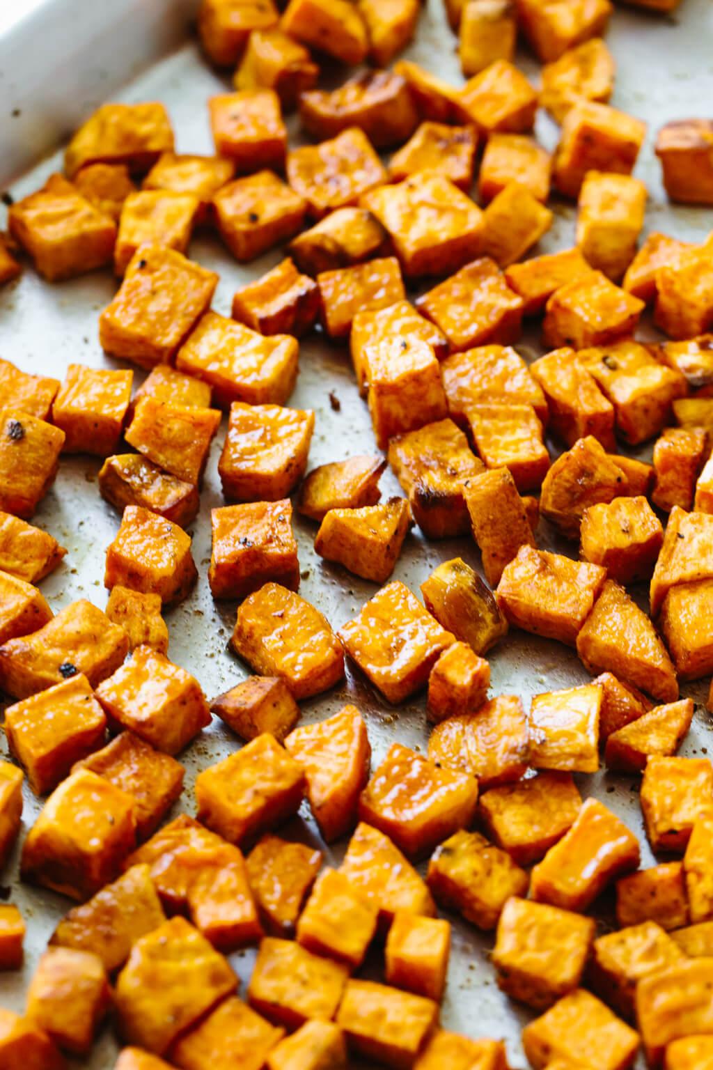 Roasted sweet potatoes on a sheet pan.