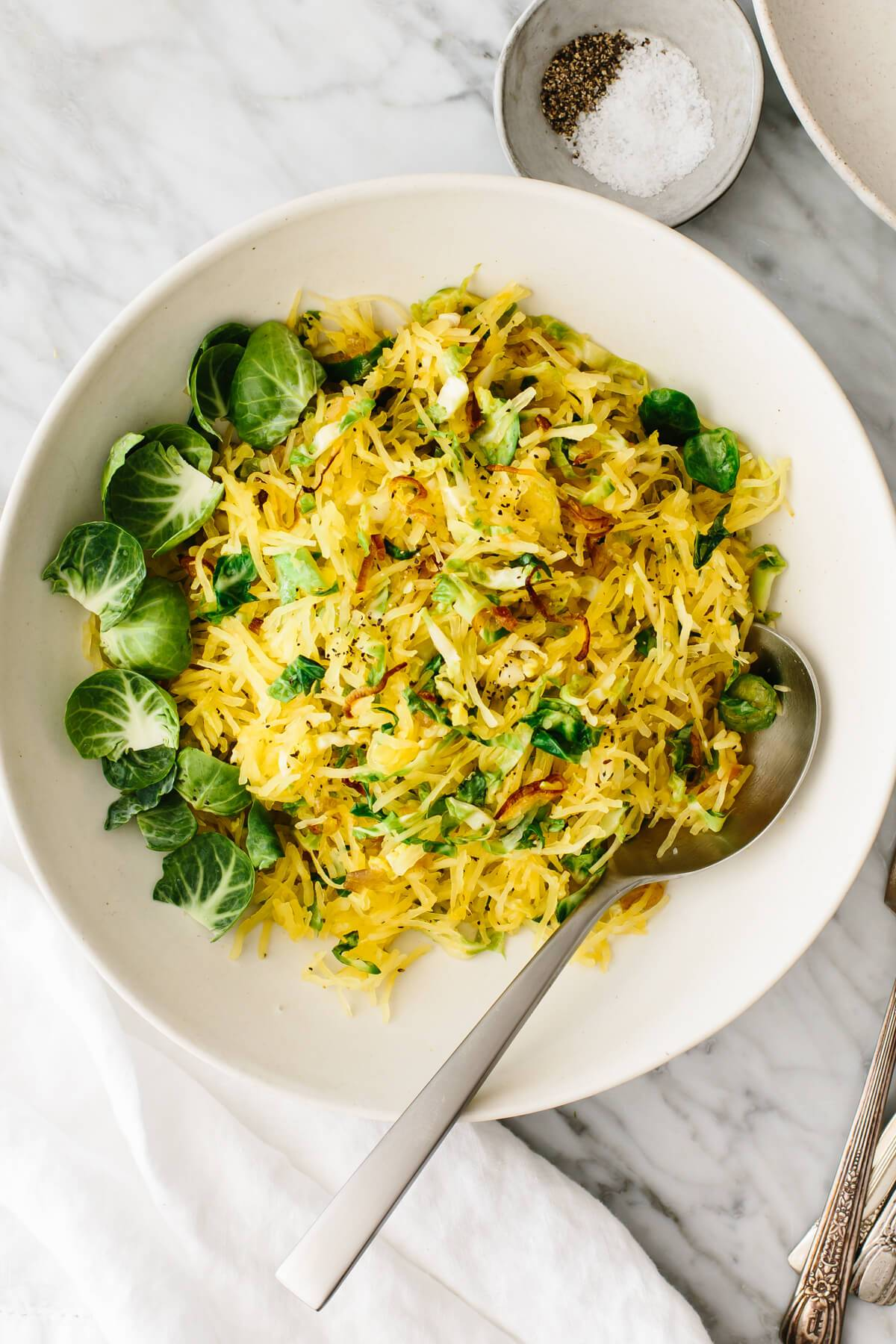 Spaghetti squash, Brussels sprouts, and crispy shallots side dish in a bowl.
