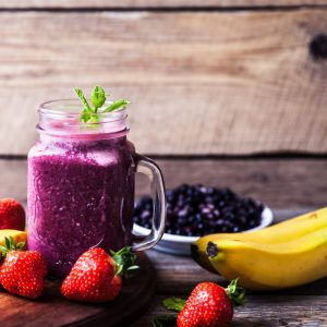 Blueberry smoothies on a wooden background with fruits. Vitamins a